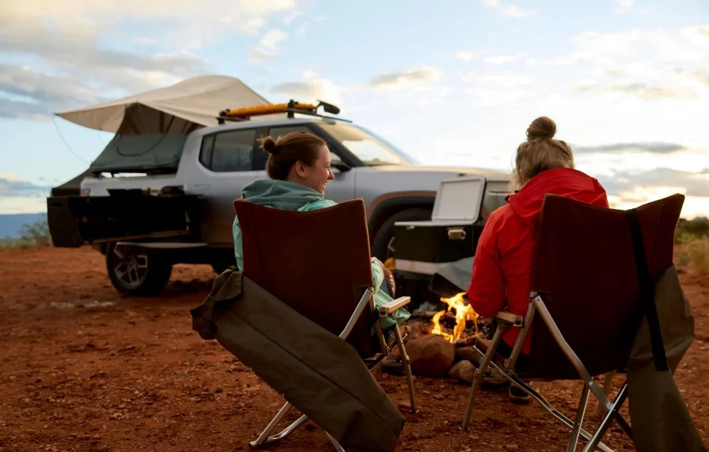 Two woman relaxing by a fire near a silver Rivian R1T