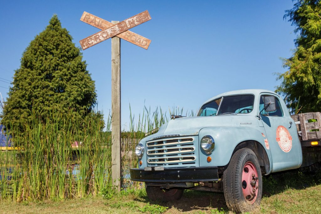A weathered blue Studebaker 2R Series pickup truck by an overgrown railroad track
