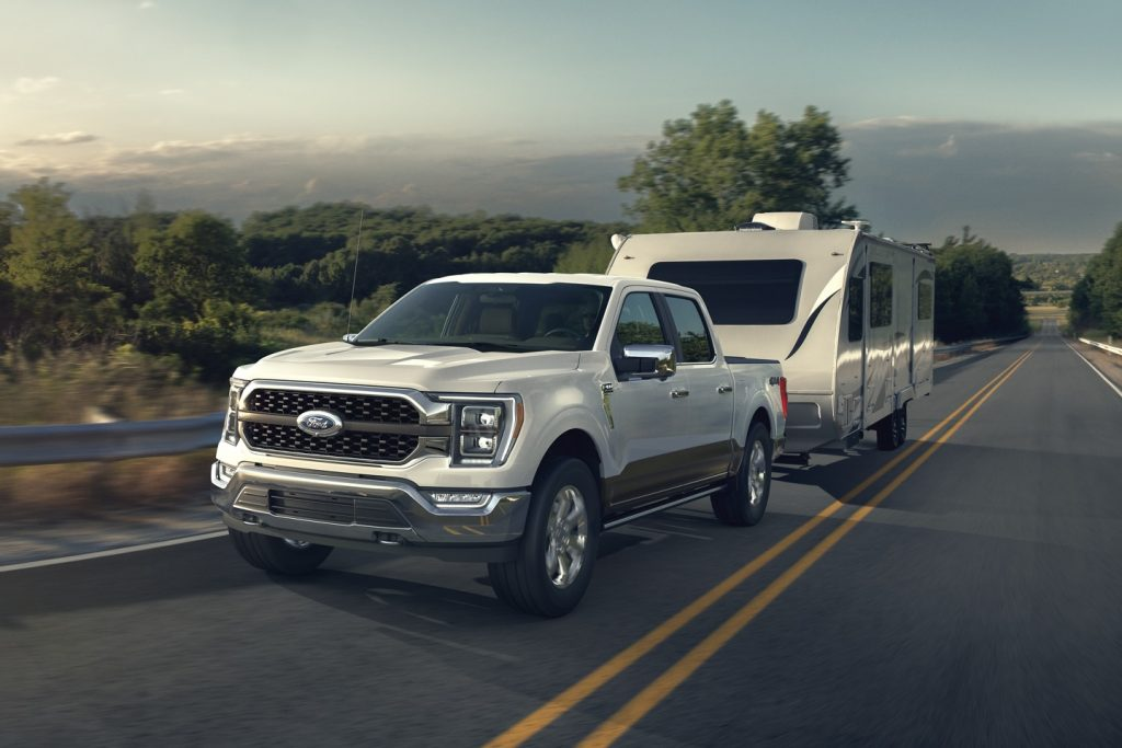 White 2021 Ford F-150 towing a camping trailer