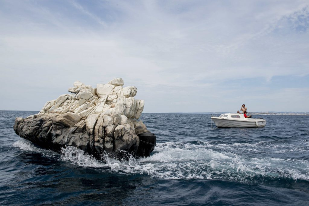 The French coast with a rock boat inconspicuously floating next to another boat