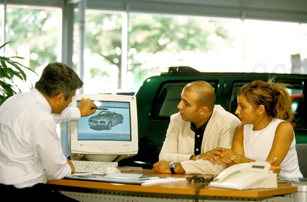 A car salesperson tells a couple of customers about the TT while sitting at his desk.