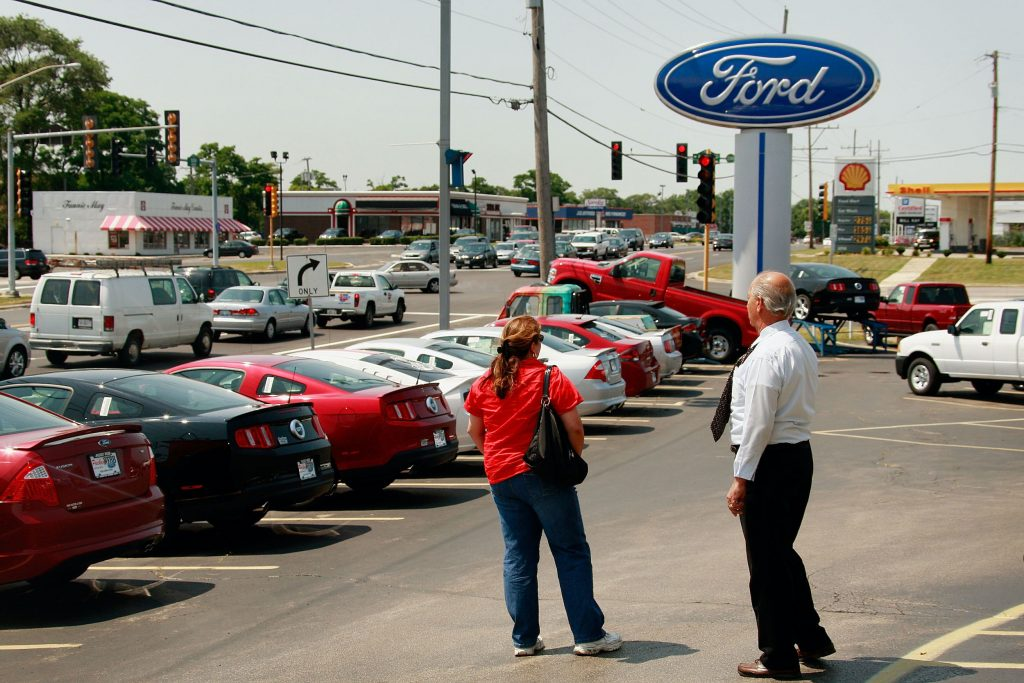 A Ford car salesperson shows a customer the lot.