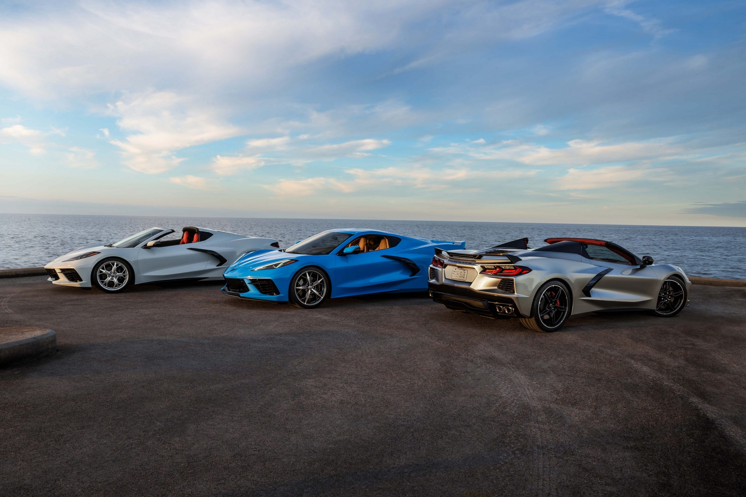 A trio of Chevrolet Corvette models shot at the 3/4 angle by the sea