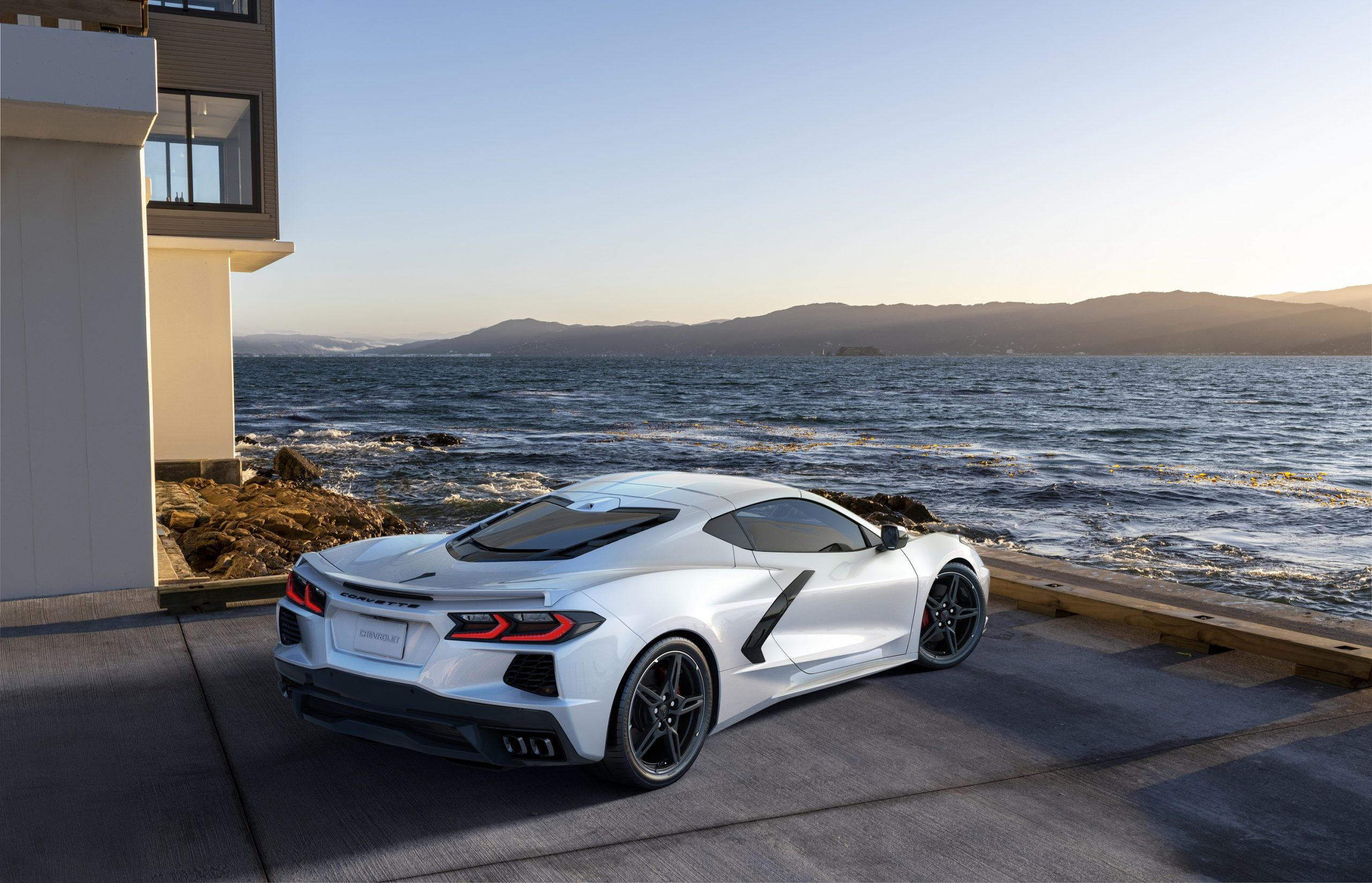The rear of the 2021 Chevrolet Corvette shot from the rear quarter while facing the sea