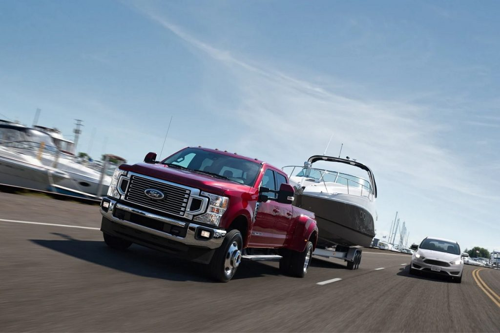 A red 2021 Ford F-450 towing a boat down the highway.