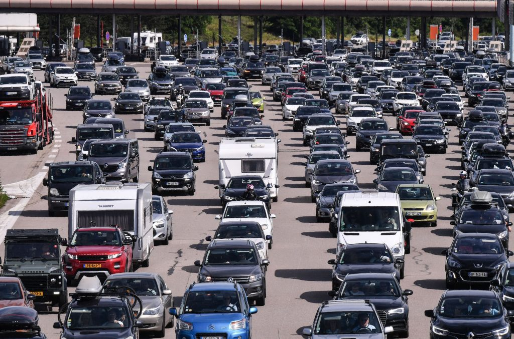 Motorists drive and queue in their vehicles at a toll station on the A7 motorway between Lyon and Vienne, southeastern France, during a heavy traffic jam on the first major weekend of the French summer holidays.