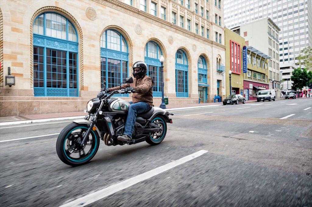 a man riding a Kawasaki Vulcan S down a city street.