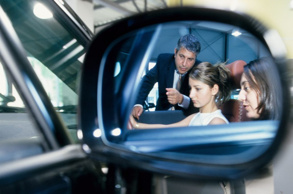 A mirror reflection view of two customers learning about the Audi TT.