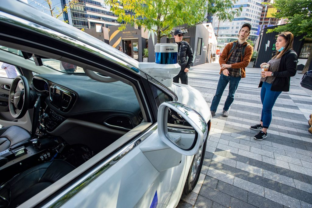Event attendees inspect an autonomous car by Motional at the Robot Block Party put on by MassRobotoics in Boston, Massachusetts on October 2, 2021.