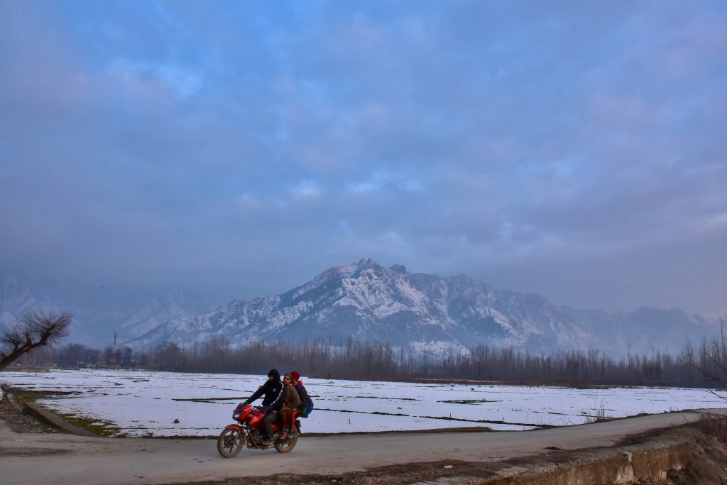 A motorcyclist rides along the road with snow-clad mountains in the backdrop during a winter evening in Srinagar. Weather across the Srinagar city has improved after Kashmir received fresh snowfall