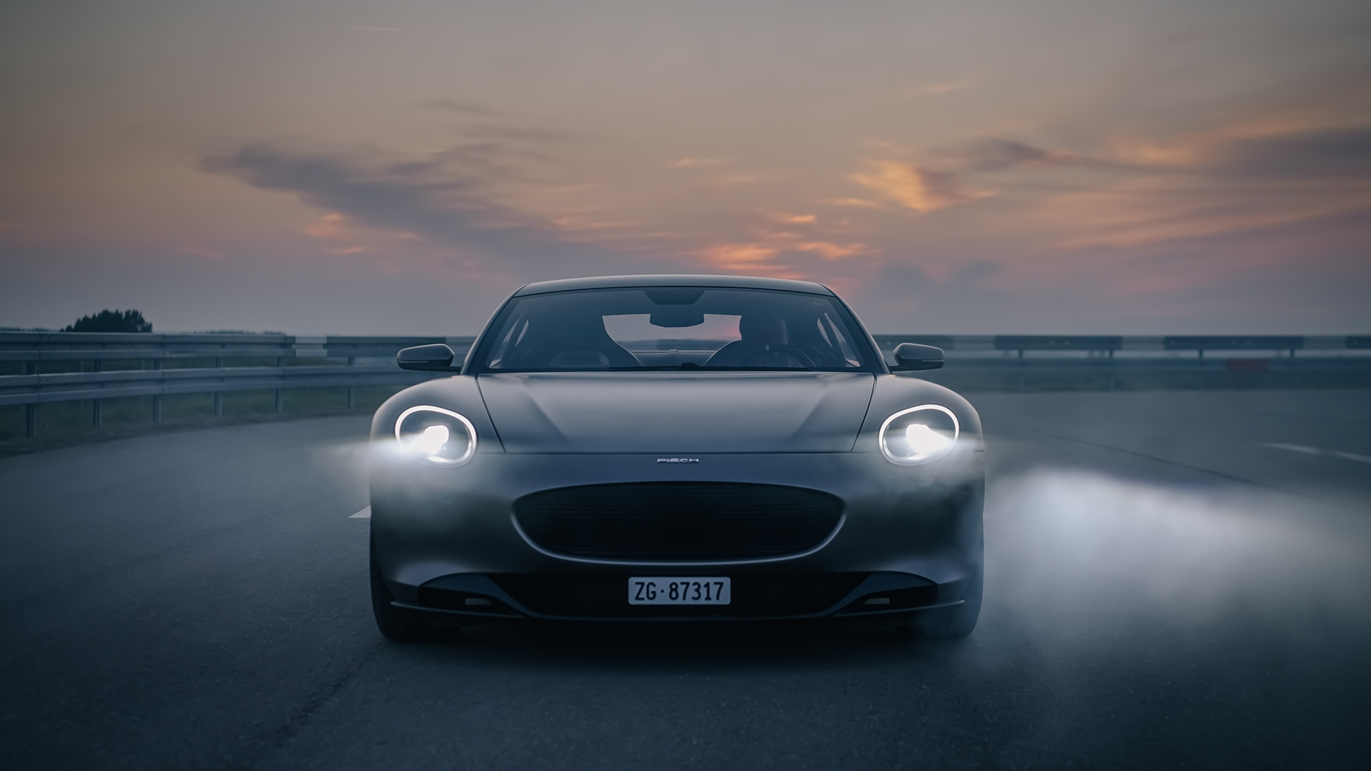 A grey Piech GT shot from the front on an airfield at dusk