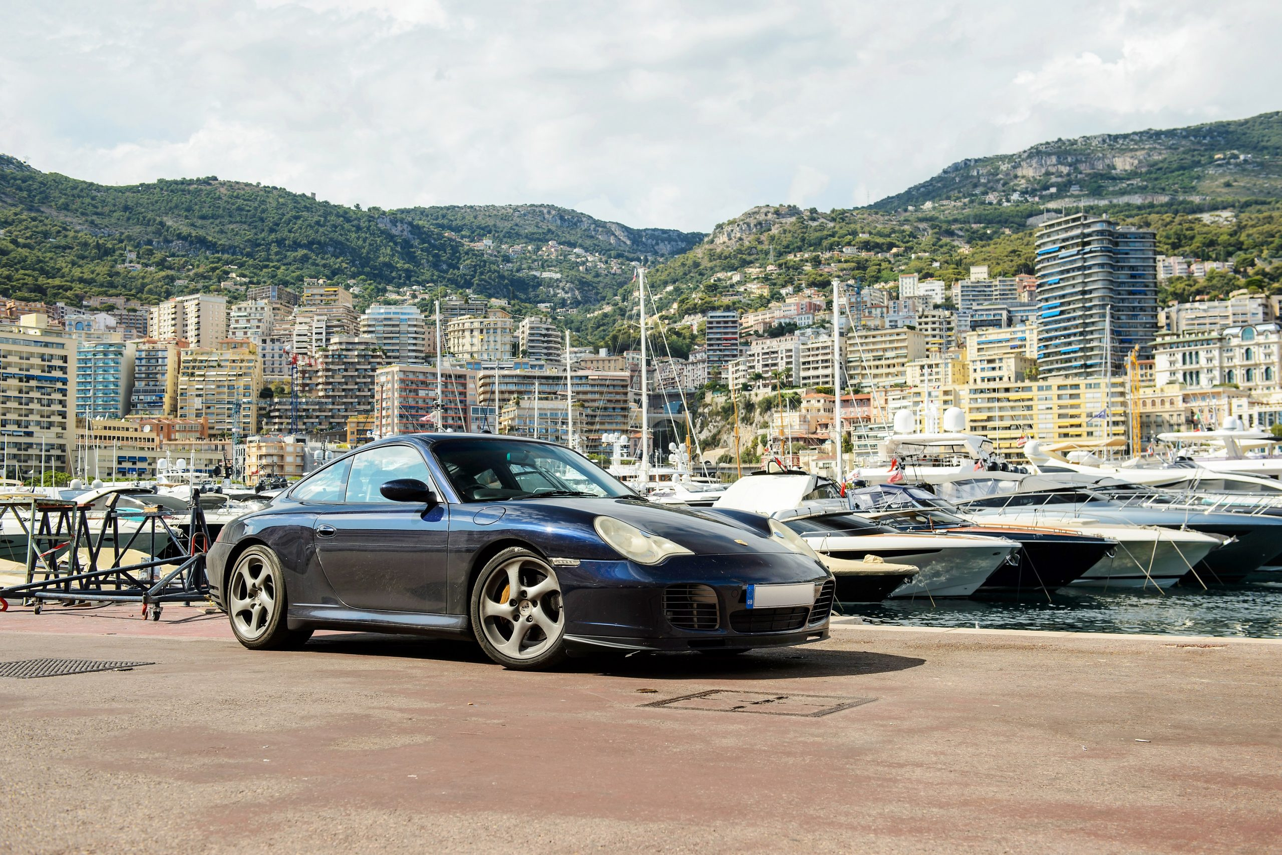 A dark blue 996 Porsche 911 on the docks in Monaco, shot from the 3/4 angle