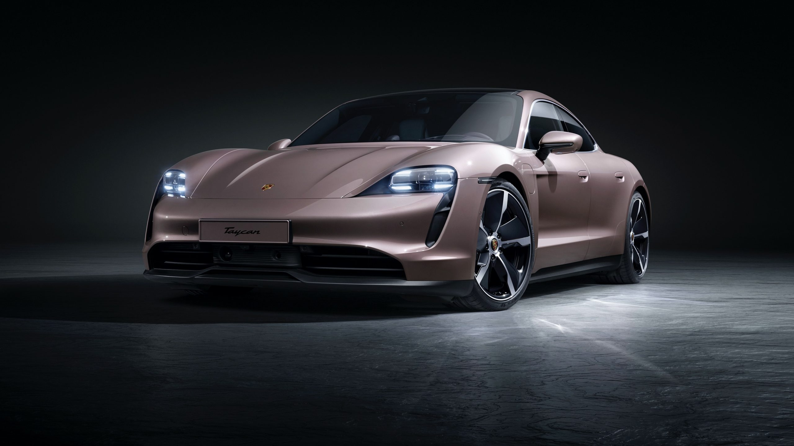 The 2021 Porsche Taycan shot from the front 3/4 in a studio with frozen berry paint