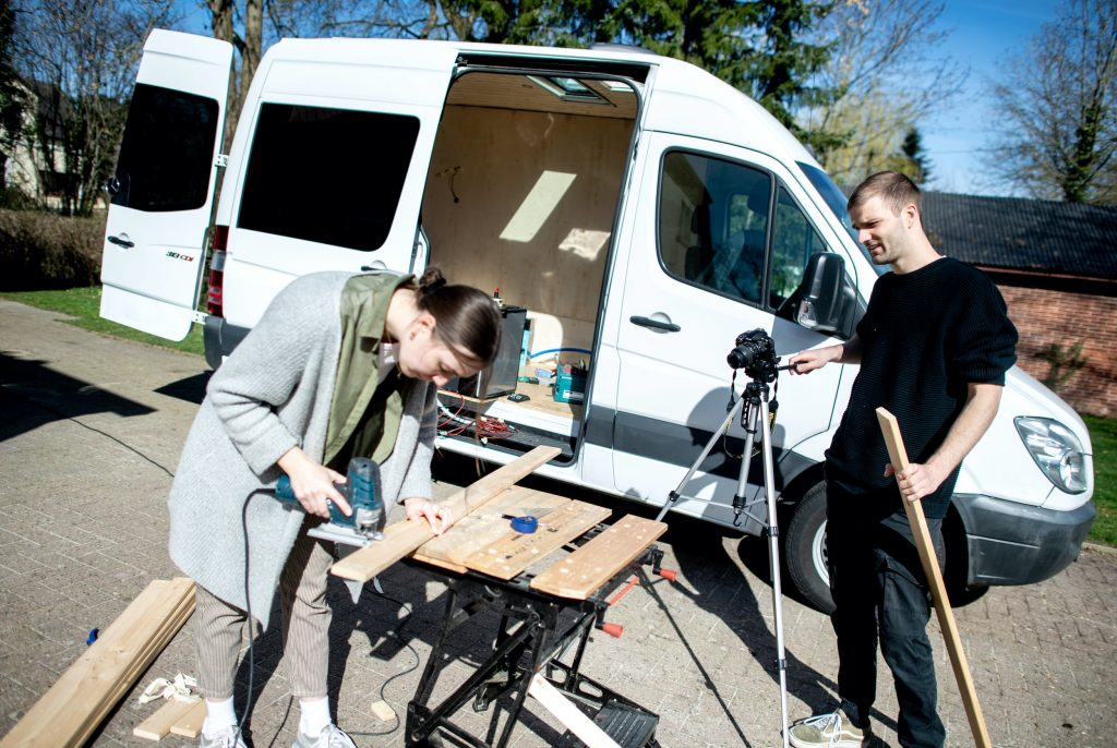 Greta Thomas and Hannes Wehrmann are cutting wood in front of their Mercedes-Benz Sprinter, which the couple is converting into a campervan.