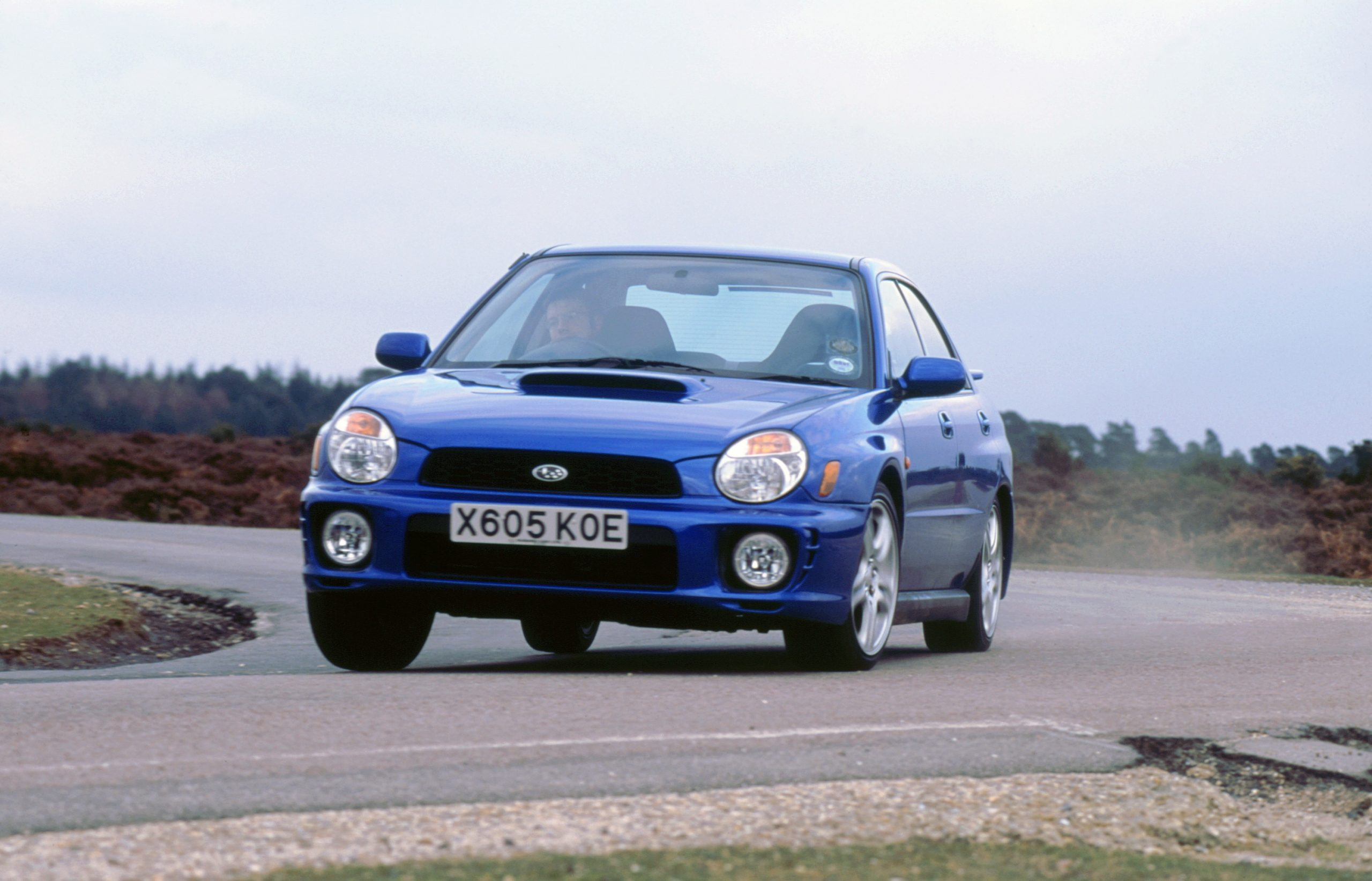 A blue Subaru WRX cornering at full speed, shot from the 3/4 angle