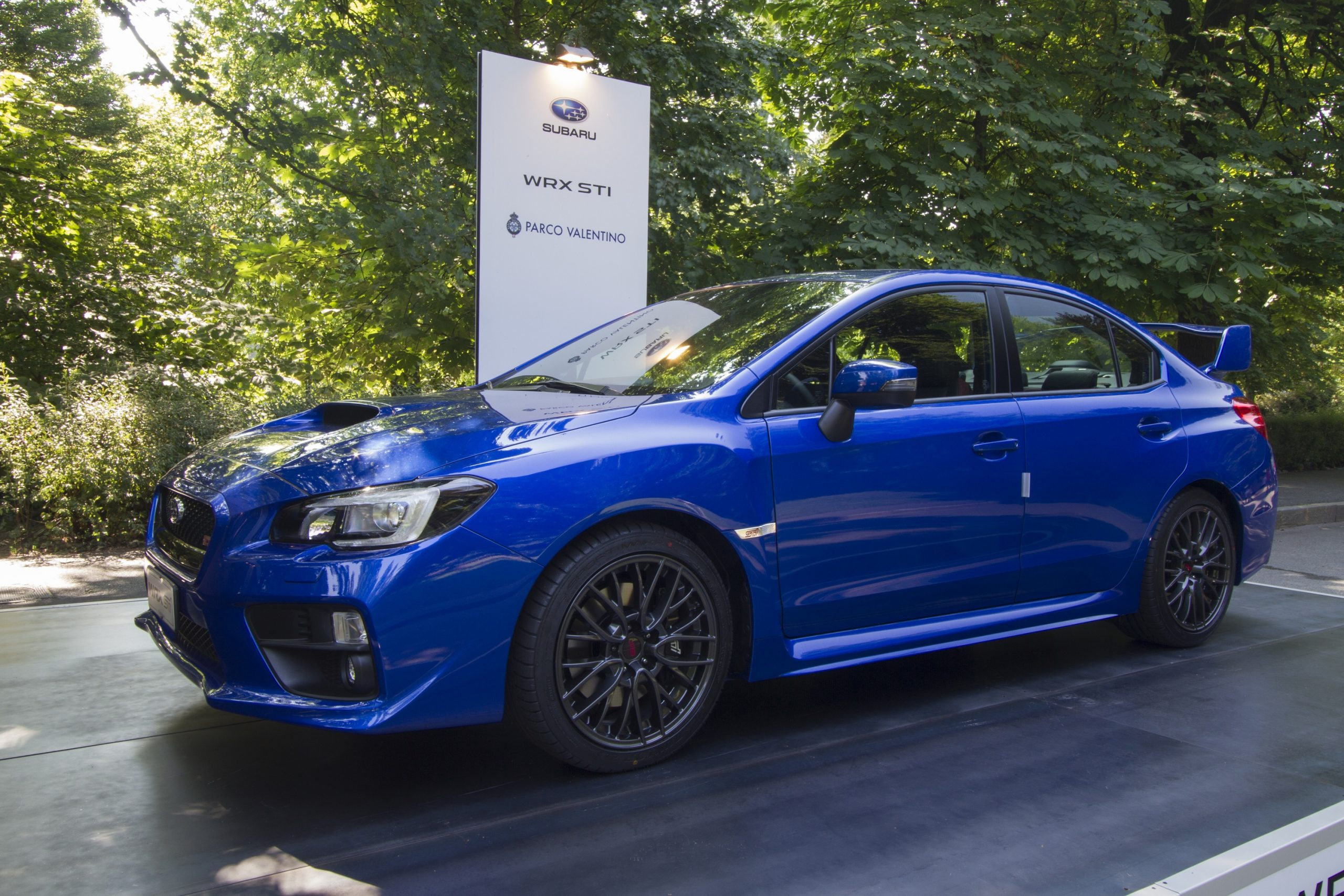 A blue Subaru WRX STI on a podium at an auto show shot from the front 3/4.