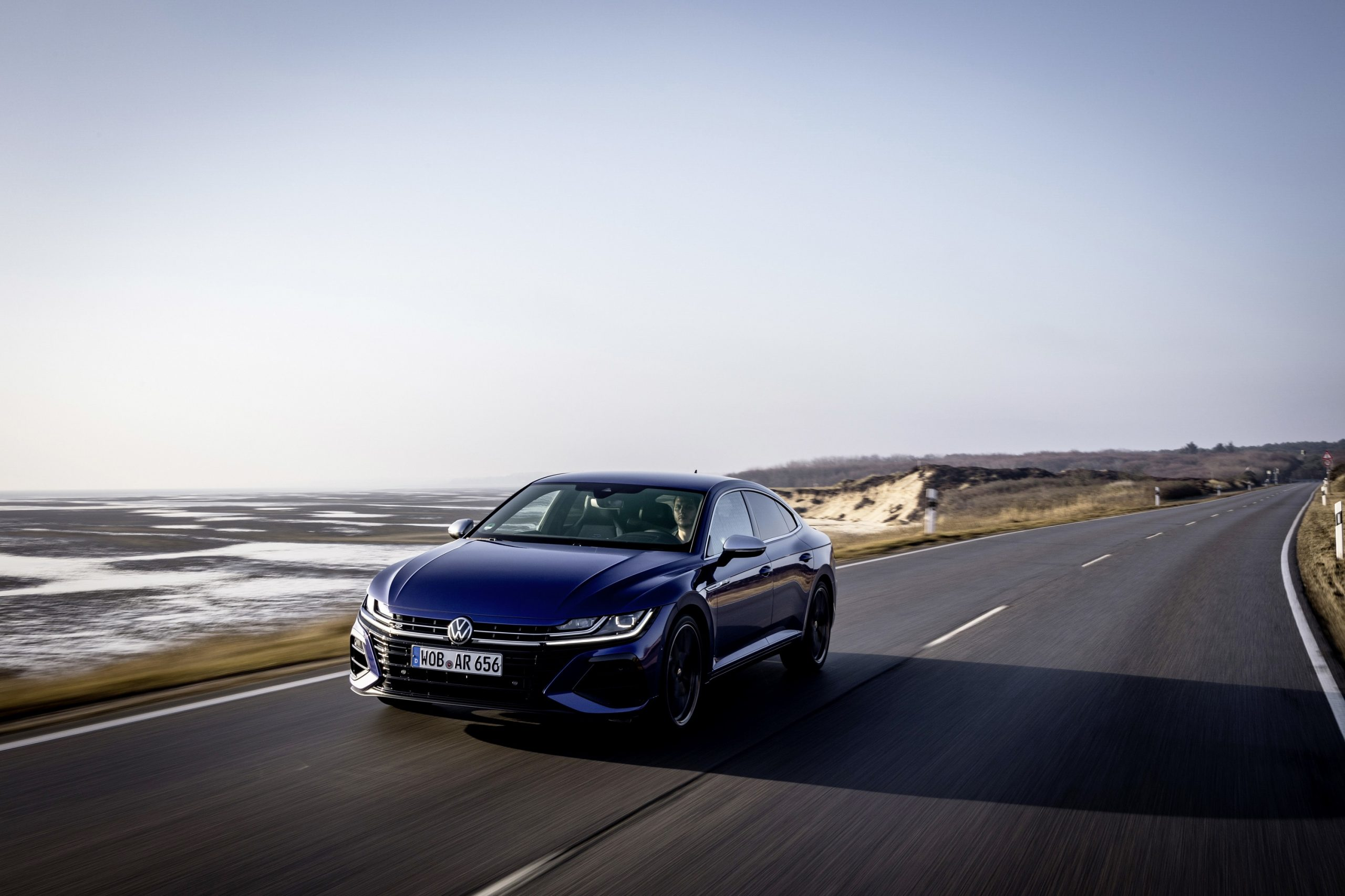 A blue Volkswagen Arteon R at the seaside