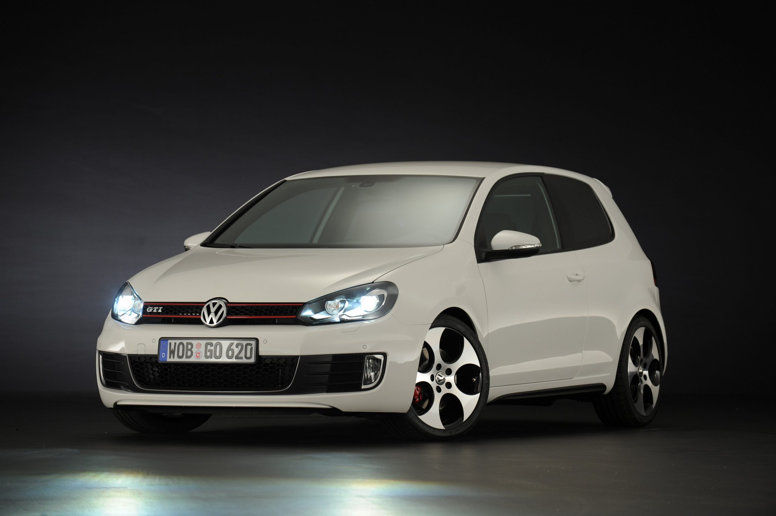 A white Volkswagen GTI shot in a photo booth from the front 3/4