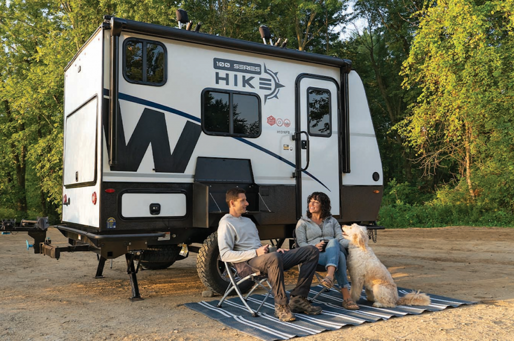a couple sitting outside the Hike 100 small camper